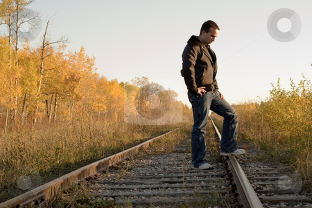 Melancholy stock photo, A man outside standing on some tracks, in a melancholy mood by Richard Nelson