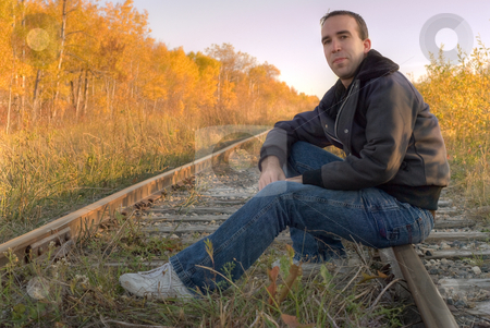 Relaxing stock photo, A man sitting on a set of railroad tracks, smiling at the camera by Richard Nelson