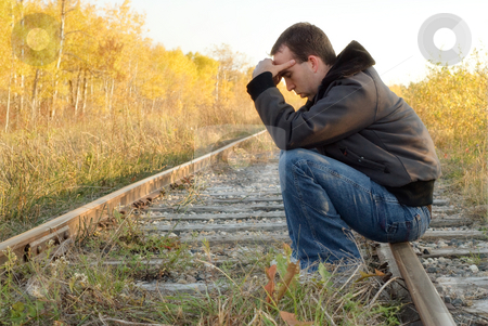 Sad Man stock photo, A sad man sitting on a set of railroad tracks doing some thinking by Richard Nelson