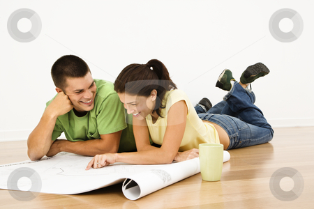 Couple planning future. stock photo, Attractive young adult couple lying on home floor with coffee cups smiling and looking at blueprints. by Iofoto Images