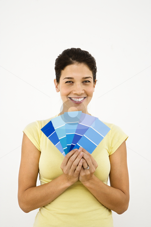 Woman with paint samples. stock photo, Pretty smiling woman holding paint sample cards in front of white wall. by Iofoto Images
