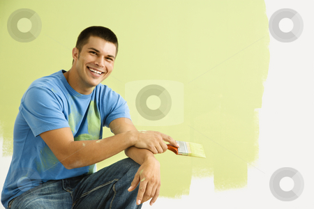 Smiling painting man. stock photo, Smiling man kneeling in front of partially painted wall holding paintbrush. by Iofoto Images