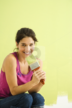Smiling woman painting. stock photo, Pretty smiling woman kneeling in front of partially painted wall holding paintbrush. by Iofoto Images