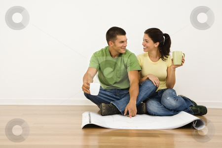 Couple renovating. stock photo, Attractive couple sitting on home floor with coffee cups looking at house plans and smiling at eachother. by Iofoto Images