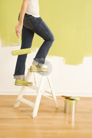 Female painter on ladder. stock photo, Legs of woman climbing stepladder holding paint roller. by Iofoto Images