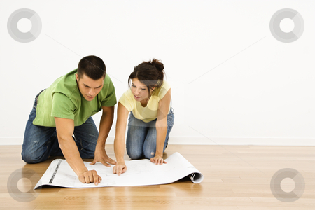 Couple with house plans. stock photo, Attractive young adult couple looking at house plans. by Iofoto Images