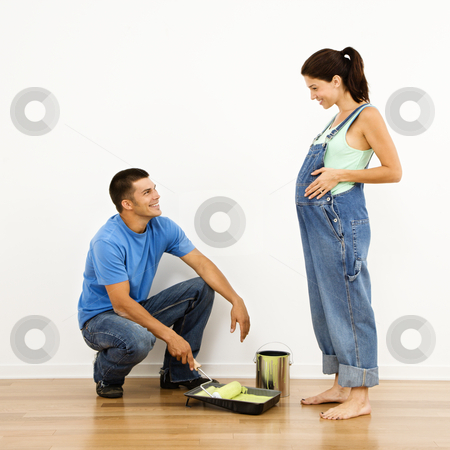 Couple preparing for baby. stock photo, Pregnant woman and husband preparing to paint interior home wall. by Iofoto Images