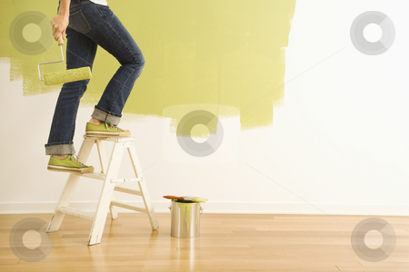 Woman painter on ladder. stock photo, Legs of woman climbing stepladder holding paint roller. by Iofoto Images