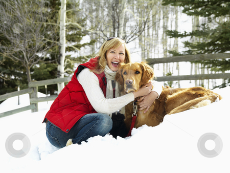 Winter portrait. stock photo, Woman hugging dog while bending down in the snow. by Iofoto Images