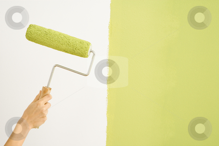 Woman painting wall. stock photo, Caucasian female hand holding paint roller next to wall half painted. by Iofoto Images