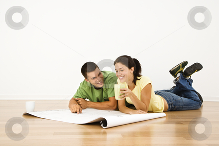 Couple making plans. stock photo, Attractive young adult couple lying on home floor with coffee cups smiling and looking at blueprints. by Iofoto Images