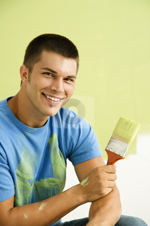 Man painting wall. stock photo, Smiling man kneeling in front of partially painted wall holding paintbrush. by Iofoto Images