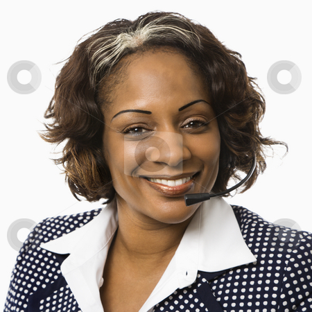 Businesswoman with headset. stock photo, Head and shoulder of smiling businesswoman talking on telephone headset. by Iofoto Images
