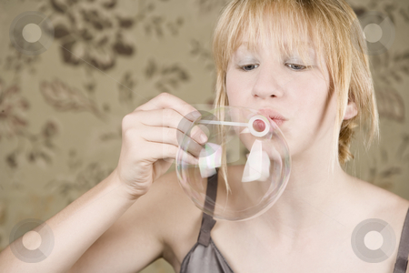 Pretty young girl blowing bubbles stock photo, Pretty young girl with blue eyes blowing a bubble by Scott Griessel