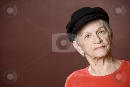 Senior woman in a Greek fishing hat stock photo, Senior woman in a red shirt and Greek fishing cap by Scott Griessel