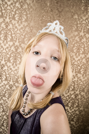 Pretty young girl with a tiara sticking her tongue out stock photo, Portrait of pretty pouting young girl wearing a tiara with her tongue out by Scott Griessel