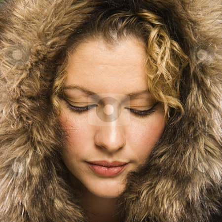 Woman with fur hood. stock photo, Caucasian young adult woman wearing fur hood with eyes closed. by Iofoto Images