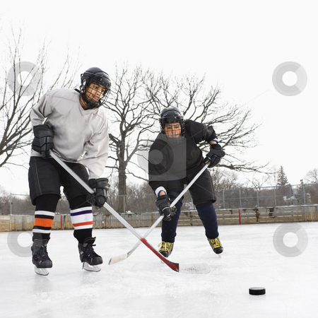 Boys playing ice hockey. stock photo, Two boys in ice hockey uniforms playing hockey on ice rink. by Iofoto Images