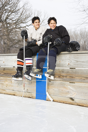 Boys in sports uniforms. stock photo, Two boys in ice hockey uniforms sitting on ice rink sidelines looking and smiling. by Iofoto Images