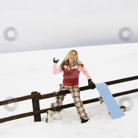 Woman throwing snowball. stock photo, Young woman in winter clothes by fence in snowy field smiling while ready to throw snowball. by Iofoto Images