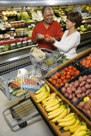 Couple grocery shopping. stock photo, Smiling middle aged African American couple comparing produce in grocery store. by Iofoto Images