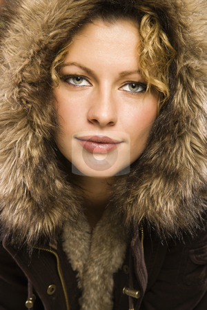 Woman with fur hood. stock photo, Caucasian young adult woman wearing coat with fur hood looking at viewer. by Iofoto Images