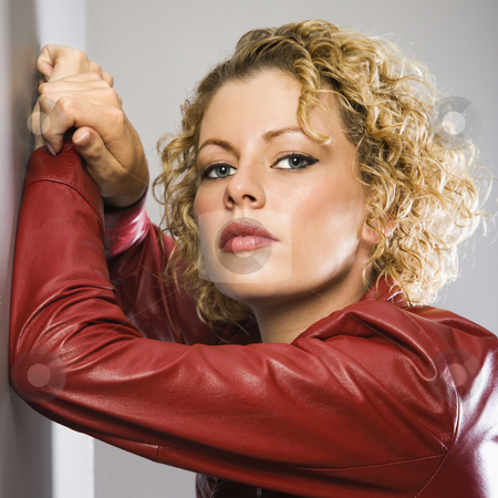Woman in red jacket. stock photo, Caucasian young adult woman in red jacket with arms raised leaning on wall looking at viewer. by Iofoto Images