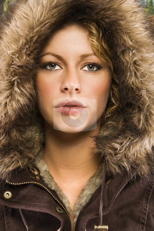 Woman in winter coat.. stock photo, Caucasian young adult woman wearing fur hood looking at viewer. by Iofoto Images