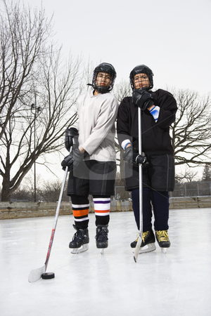 Ice hockey player boys. stock photo, Two boys in ice hockey uniforms holding hockey sticks standing on ice rink in ice skates. by Iofoto Images