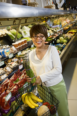 Woman in supermarket. stock photo, Middle aged African American woman in grocery store holding produce smilling at viewer. by Iofoto Images