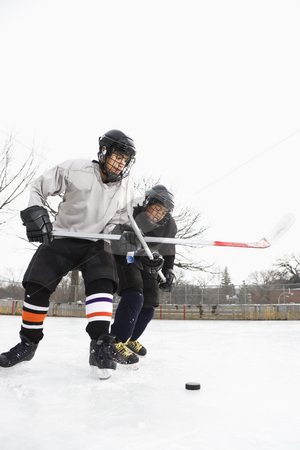 Ice hockey players. stock photo, Two boys in ice hockey uniforms playing hockey on ice rink. by Iofoto Images