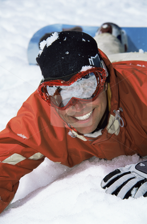 Young snowboarder lying in the snow stock photo,  by Monkey Business Images