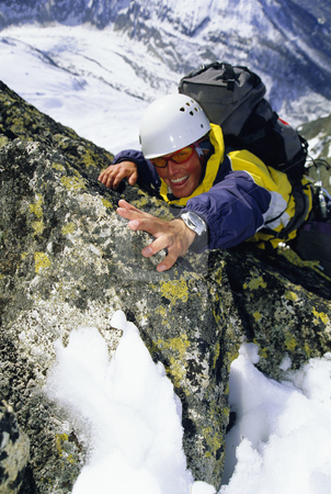 Mountaineer climbing stock photo, Mountaineer climbing snowy rock face by Monkey Business Images