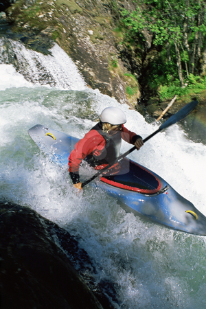 Kayaking in rapids stock photo, Young woman kayaking in rapids by Monkey Business Images