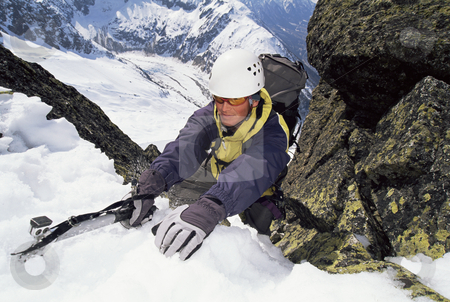 Mountaineer  stock photo, Mountaineer using an ice axe to climb a steep slope by Monkey Business Images
