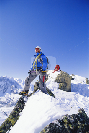 Mountain climbing on snowy peak stock photo, Young men mountain climbing on snowy peak by Monkey Business Images