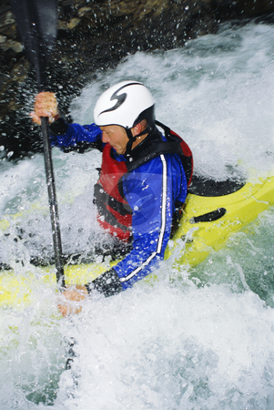 Man kayaking in rapids stock photo, Man white water kayaking in rapids by Monkey Business Images