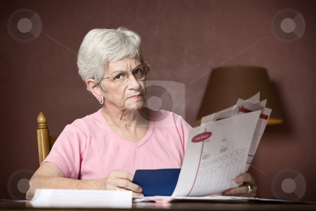 Senior woman paying bills stock photo, Upset senior woman with many bills and notices by Scott Griessel