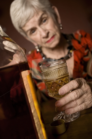Eldery alcoholic woman stock photo, Senior woman alcoholic with a bottle of booze by Scott Griessel