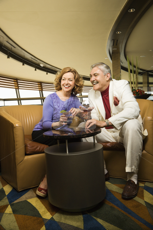 Mature couple dating. stock photo, Mature Caucasian couple sitting in bar lounge having drinks and smiling. by Iofoto Images