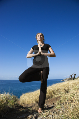 Woman practicing yoga. stock photo, Caucasian mid-adult woman standing on Hawaiian coast in Yoga tree position. by Iofoto Images