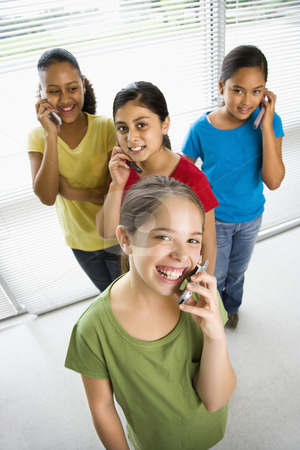 Girls on cell phones. stock photo, Preteen girls of mutiple ethnicities talking on cell phones and looking at viewer. by Iofoto Images