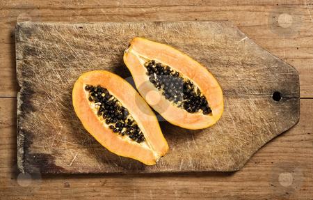 Papaya fruit sliced stock photo, Papaya fruit sliced on a wooden cutting table by Pablo Caridad