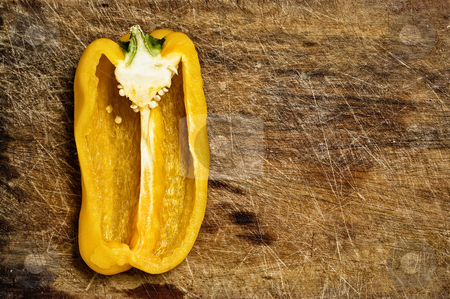 Yellow bell pepper. stock photo, Yellow bell pepper cut on a wooden cutting table. by Pablo Caridad