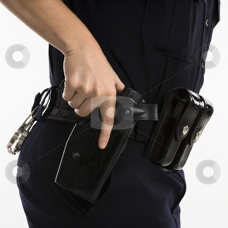 Armed policewoman. stock photo, Close up side view of mid adult female Caucasian law enforcement officer hand on gun in holster. by Iofoto Images