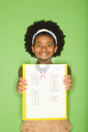 Girl with good grade. stock photo, African American girl holding out graded school assignment smiling proudly at viewer. by Iofoto Images