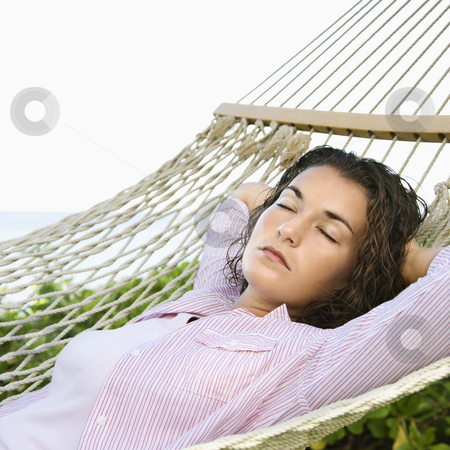 Pretty woman sleeping. stock photo, Pretty young adult Caucasian brunette female lying in hammock with arms behind head sleeping. by Iofoto Images