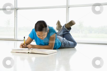 Preteen girl. stock photo, Asian preteen girl lying on floor doing homework. by Iofoto Images