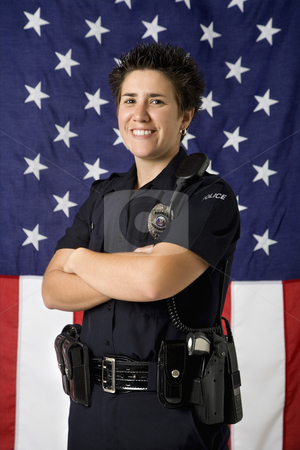 Policewoman and flag. stock photo, Portrait of mid adult Caucasian policewoman standing with arms crossed with American flag as backdrop smiling at viewer. by Iofoto Images