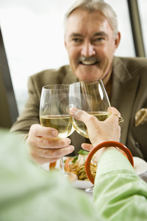 Mature couple toasting. stock photo, Mature couple dining and toasting in fancy restaurant. by Iofoto Images